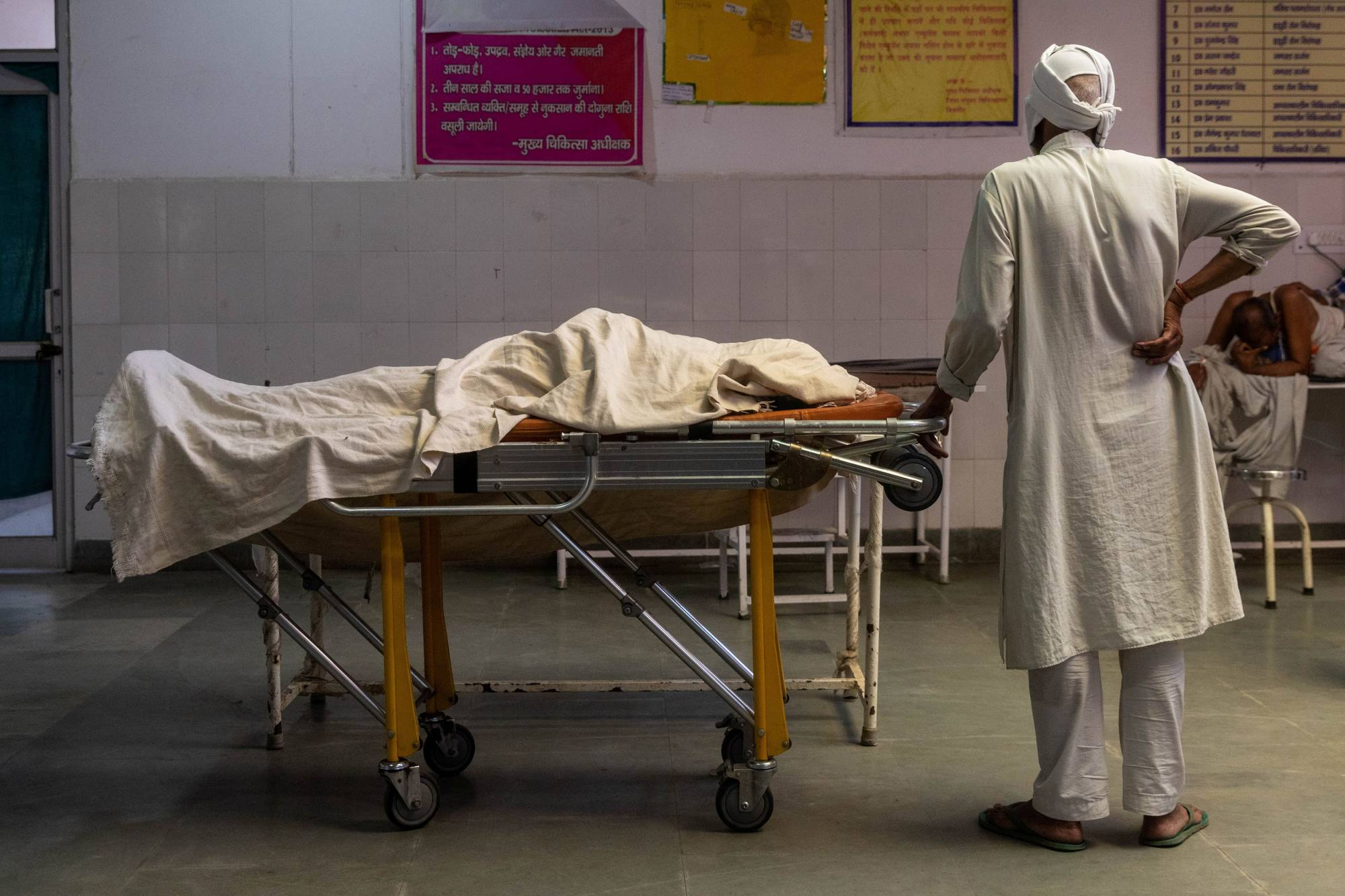 A man stands next to the body of his wife, who died due to breathing difficulties, inside an emergency ward of a government-run hospital in Bijnor, India, on Tuesday.  | REUTERS