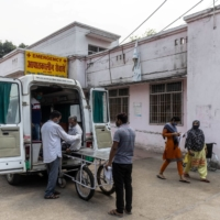 Relatives help Jagdish Singh, 57, out of an ambulance outside a government-run hospital in Bijnor, India, on Tuesday.  | REUTERS
