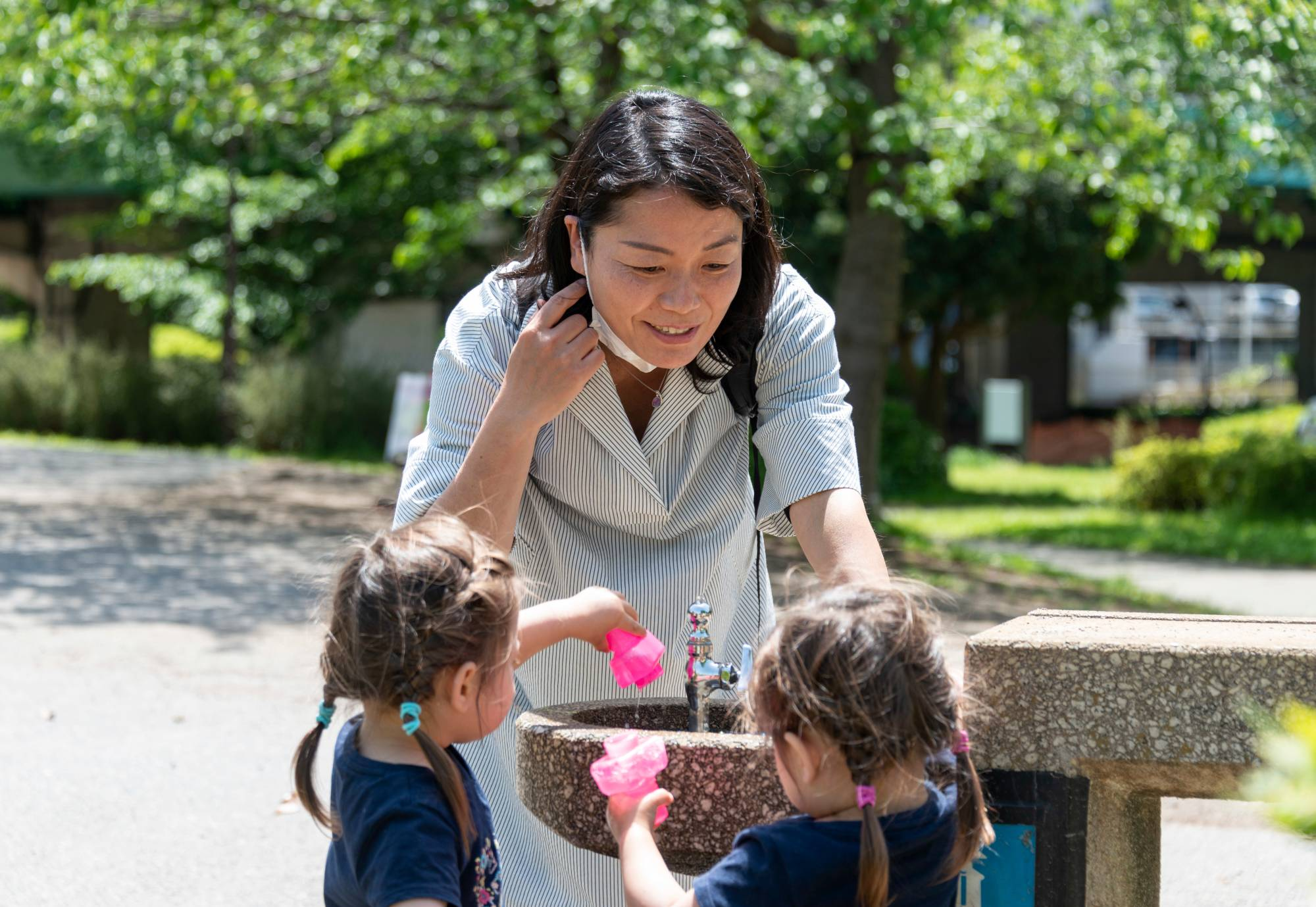 Kaoru Suzuki-Houghton plays with her 2-year-old twin daughters, Sophia and Malia, at a park in Tokyo in April. | ROB GILHOOLY