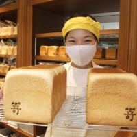 A worker shows loaves of Sakimoto bread in Nagoya. | KYODO