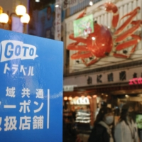 A poster for the government's Go To Travel tourism campaign is displayed on a street in Osaka in November 2020.   KYODO