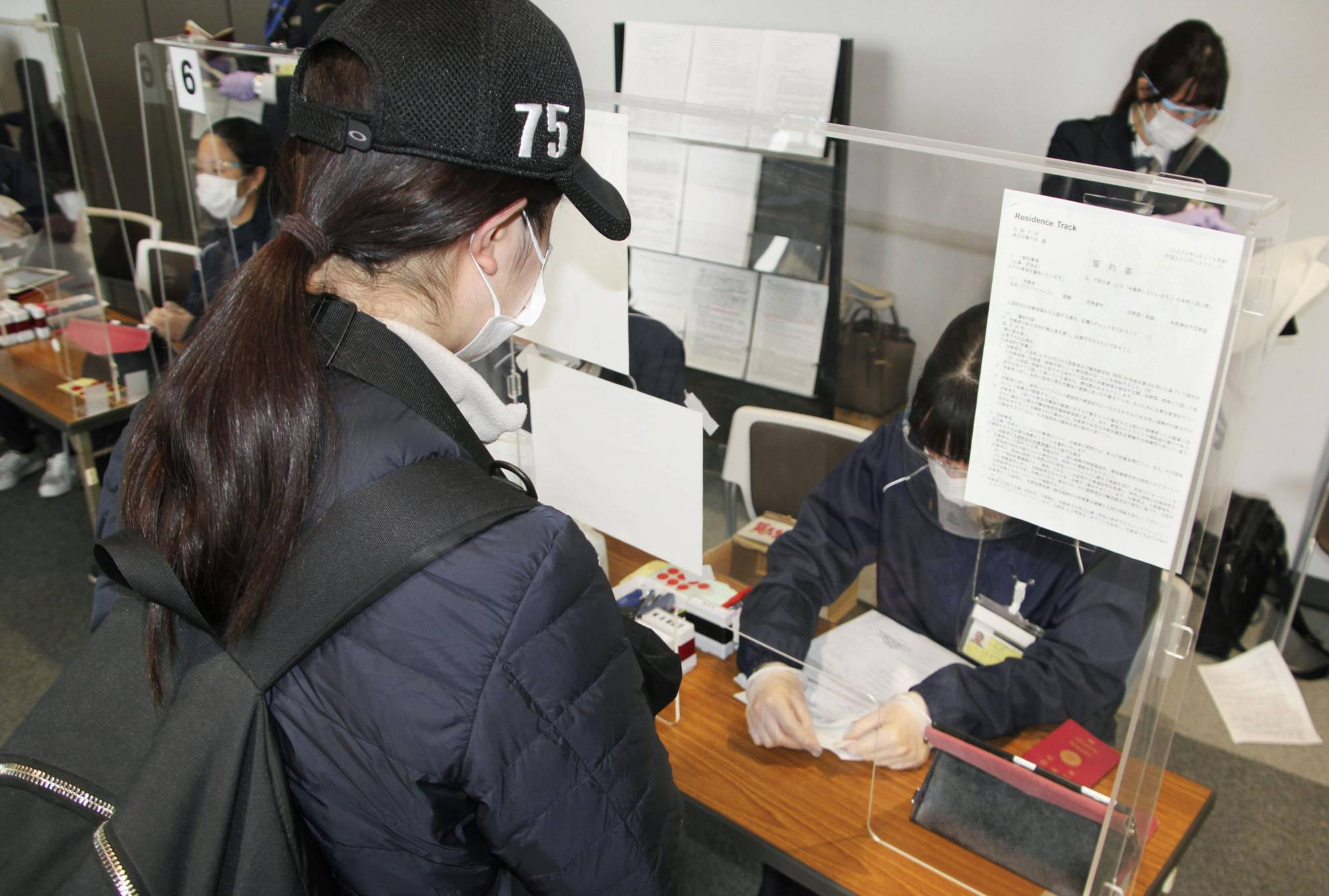 An arriving passenger submits test certificates at Narita Airport in Chiba Prefecture on April 19. | KYODO