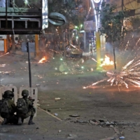 Palestinians clash with Israeli security forces in the center of the West Bank town of Hebron on Wednesday.   AFP-JIJI