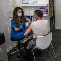 Health care workers prepare to administer COVID-19 vaccine doses at a mass vaccination center in Barcelona on May 2. | BLOOMBERG