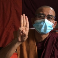 Buddhist monk Shwe Ohh Sayardaw, who has taken part in demonstrations with protesters against the military coup, makes a three-finger salute as he speaks during an interview in April at a monastery in Yangon, where he is hiding from authorities. | AFPTV / VIA AFP-JIJI