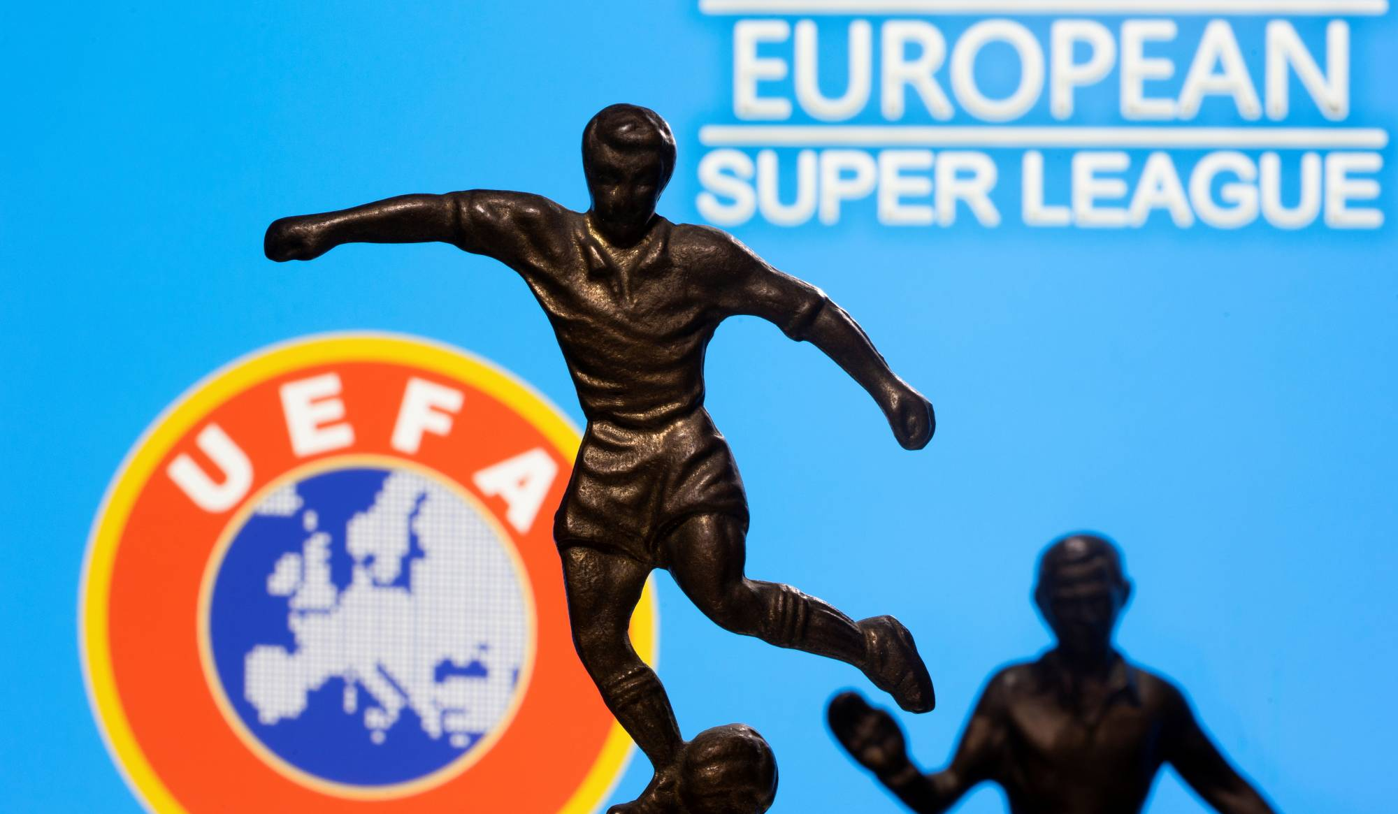 Metal figures of soccer players are seen in front of the words 'European Super League' and the UEFA logo in an illustration taken April 20.   REUTERS