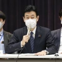 Yasutoshi Nishimura, the minister leading the government's COVID-19 response, speaks at a meeting of experts on the coronavirus in Tokyo on Friday morning. | KYODO