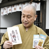Tour guide: Daien Oshita, chief priest of Senkoji temple in Takayama, Gifu Prefecture, shows off the temple's 'Sukuna' seal stamp and good-luck charms. | KYODO