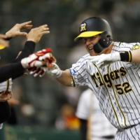 The Tigers' Jerry Sands celebrates with his teammates after giving Hanshin the lead with a solo home run in the eighth inning on Thursday at Koshien Stadium. | KYODO