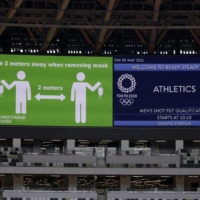 An image reminding fans to maintain social distance is displayed on a video board at National Stadium during a test event on Sunday. | KIYOSHI OTA / BLOOMBERG