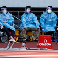 Medical officers wearing protective suits watch an athletics test event at National Stadium on Sunday. | REUTERS