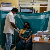 A woman receives a dose of Covishield, a COVID-19 vaccine manufactured by Serum Institute of India, at a vaccination center in Bangalore on Thursday. | REUTERS