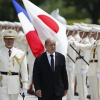Then-French Defense Minister Jean-Yves Le Drian reviews an honor guard at the Defense Ministry in Tokyo in July 2014.   | REUTERS