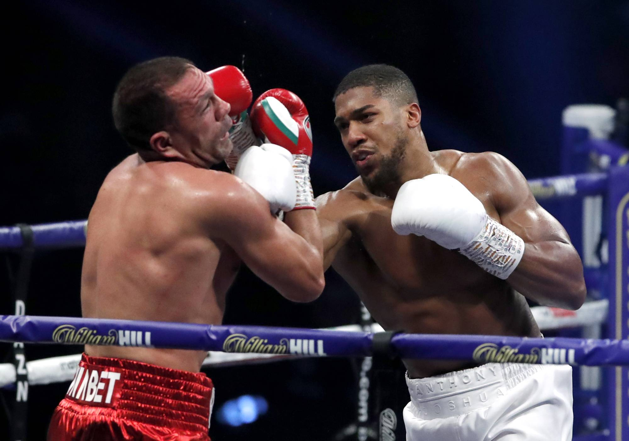 Anthony Joshua punches Kubrat Pulev during their heavyweight world title fight in London on Dec. 12, 2020. | POOL / VIA REUTERS