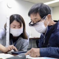 A city official teaches an older man how to use a smartphone to reserve a COVID-19 vaccine shot at a municipal office in Okazaki, Aichi Prefecture, on Thursday. | KYODO