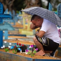 A man cries by a grave at the Nossa Senhora Aparecida cemetery on Mothers Day in Manaus, Brazil.  | AFP-JIJI