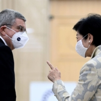 Tokyo Gov. Yuriko Koike speaks with International Olympic Committee chief Thomas Bach during a meeting in Tokyo in November.