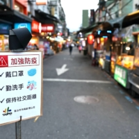 A sign reminding people to wear protective face masks, wash their hands and maintain social distancing at a night market in Taipei on Saturday   REUTERS