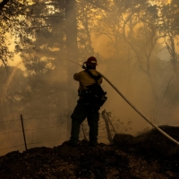 A private firefighter monitors a backfire during the Glass Fire in Calistoga, California, in October of last year. | REUTERS