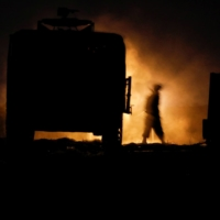 An Israeli soldier walks next to a military vehicle at a mobile artillery unit location at Israel's border with the Gaza Strip on Sunday. | REUTERS