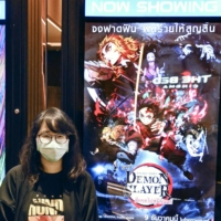 A woman poses for a photo at a movie theater in Bangkok on Dec. 9, the opening day of the blockbuster animated film 'Demon Slayer,' based on the namesake Japanese manga series, in Thailand. | KYODO