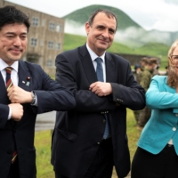 State Minister of Defense Yasuhide Nakayama, French Ambassador to Japan Philippe Setton and Australian Ambassador to Japan Jan Adams pose for pictures during a joint military drill between the Self-Defense Forces, French army and U.S. Marines, at the Kirishima exercise area in Ebino, Miyazaki Prefecture, on Saturday.   POOL / VIA REUTERS
