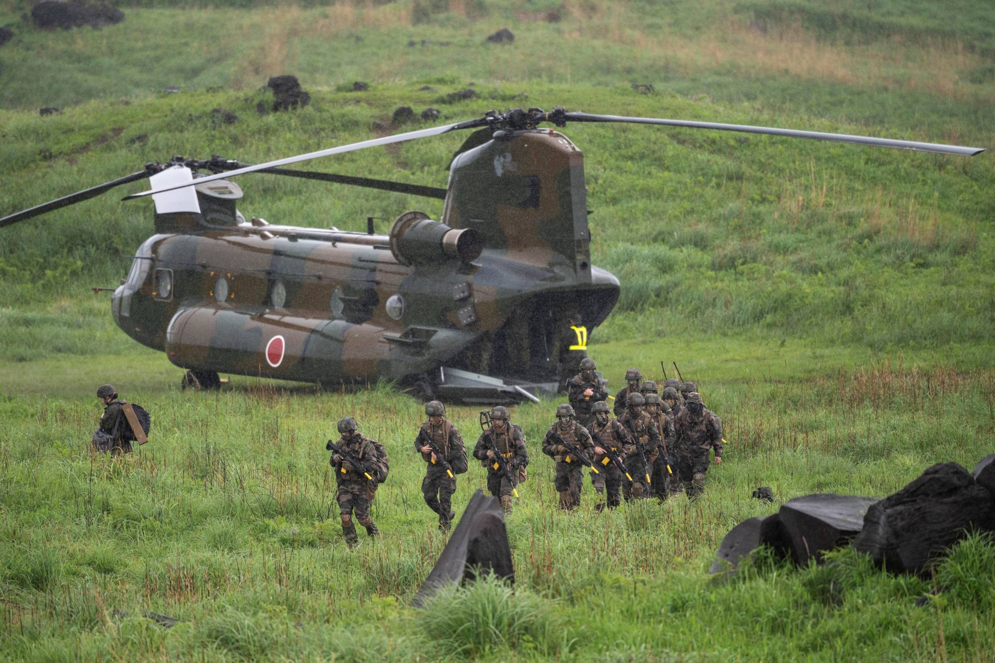 French soldiers walk away from a Chinook helicopter during a joint military drill between the Self-Defense Forces, French army and U.S. Marines at the Kirishima exercise area in Ebino, Miyazaki Prefecture, on Saturday.   POOL / VIA REUTERS