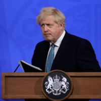 British Prime Minister Boris Johnson leaves after giving an update on the coronavirus pandemic during a virtual news conference in London on Friday. | POOL / VIA AFP-JIJI