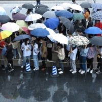 People line up in the rain to get vaccinated against the coronavirus outside an inoculation site in Fuyang, in China's Anhui province, on Saturday.    CHINA DAILY / VIA REUTERS