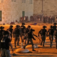 Israeli security forces advance amid clashes with Palestinian protesters at the Al-Aqsa mosque compound in Jerusalem on May 7. | AFP-JIJI
