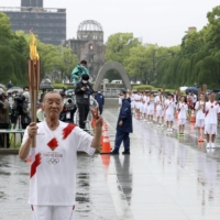 Takayuki Sakai (left) and other runners participate in a torch relay ceremony at the Peace Memorial Park in Hiroshima on Monday.