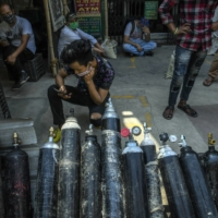 People wait in New Delhi for oxygen cylinders to be refilled on May 3. | ATUL LOKE / THE NEW YORK TIMES