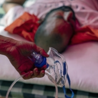 A heath worker prepares to supply free oxygen for a coronavirus patient in Uttar Pradesh, India on May 11. | BLOOMBERG