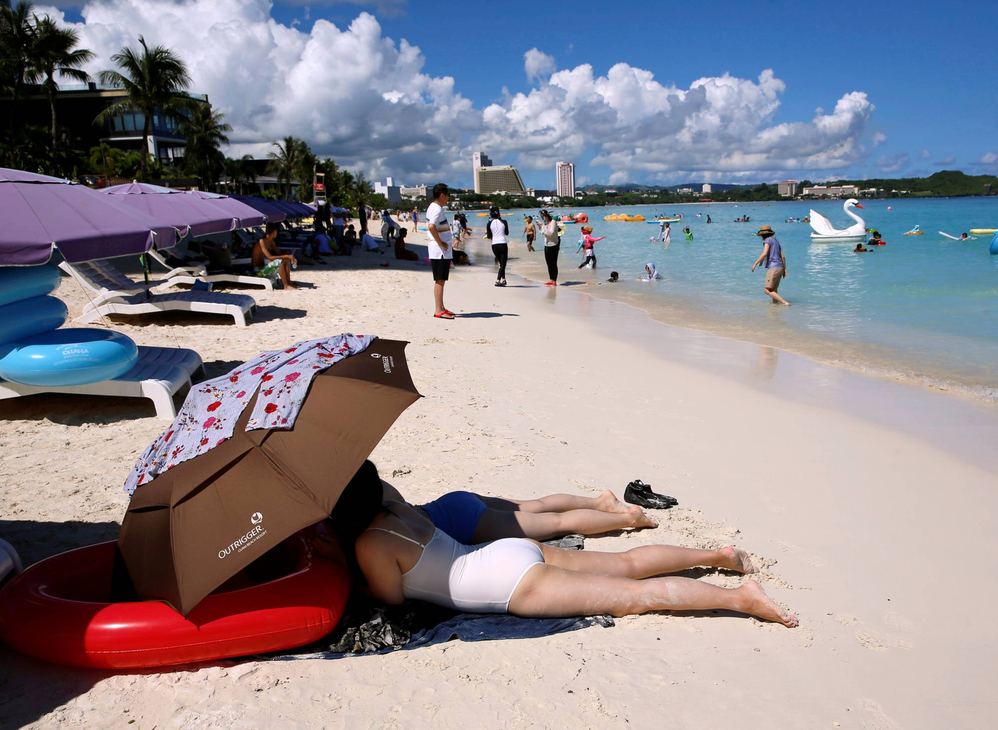 Tourists on a beach in Guam in 2017. The island's 'Air V&V' program applies to all Americans, including adolescents, with valid residency in Japan, Taiwan, Hong Kong and several other Asian countries.   REUTERS