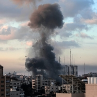 Smoke rises from a building in Gaza City, Gaza Strip, on Tuesday following an Israeli airstrike.    HOSAM SALEM / THE NEW YORK TIMES