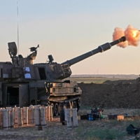 Israeli soldiers fire a 155 mm self-propelled howitzer toward the Gaza Strip from their position along the border on Tuesday. | AFP-JIJI