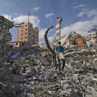 A Palestinian youth looks for salvageable items amid the rubble of the Kuhail building, which was destroyed in an early morning Israeli airstrike on Gaza City on Tuesday. | AFP-JIJI
