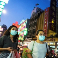People wearing face masks shop for street food in Chinatown amid the spread of the coronavirus disease (COVID-19) in Bangkok.   REUTERS