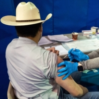 A health care worker administers a dose of the Pfizer COVID-19 vaccine at the University of New Mexico's Gallup campus on March 23.   BLOOMBERG