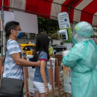 A health care worker checks the temperature of a girl entering a COVID-19 testing site in Taipei on Monday. | BLOOMBERG
