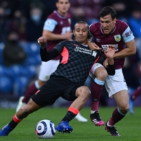 Liverpool's Thiago Alcantara (left) and Burnley's Jack Cork vie for the ball during their match on Wednesday in Burnley, England. | AFP-JIJI