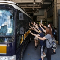 Supporters bid farewell as a prison van transports Tong Ying-kit, who was charged under the national security law, in Hong Kong in August 2020. | REUTERS