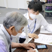 A city employee shows a man how to make a reservation for a vaccination in Okazaki, Aichi Prefecture, on May 13. | KYODO