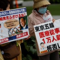 Anti-Olympics protesters hold banners denouncing the government's requests for doctors and nurses to be dispatched to help out with the games, during a rally in Tokyo on Tuesday.    REUTERS