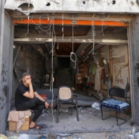 A Palestinian shop owner sits amongst the ruins of his store in the al-Rimal commercial district in Gaza City on Saturday.  | AFP-JIJI