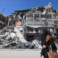 A woman walks past a destroyed building in the al-Rimal commercial district in Gaza City on Saturday. | AFP-JIJI