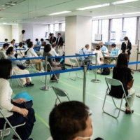 Participants take part in a coronavirus vaccination simulation by the Self-Defence Forces at an inoculation cener in Tokyo on Friday. Tokyo reported 535 new COVID-19 cases on Sunday. | AFP-JIJI