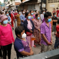 People stand behind a lockdown barrier to ask for food donations after their village had been closed for more than two weeks as part of anti-COVID-19 measures near Phnom Penh on April 30. | REUTERS