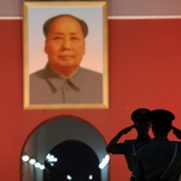 Paramilitary policemen salute each other under a giant portrait of late Chinese leader Mao Zedong at the Tiananmen gate in Beijing in June 2016.      REUTERS