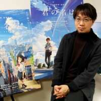 Anime director Makoto Shinkai poses for a photo in front of posters of his animated film 'Your Name' in November 2016. | REUTERS